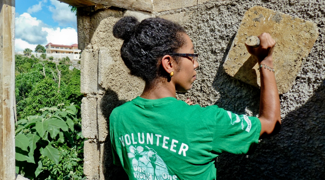 A group of volunteers works together to construct and plaster a house as part of building volunteer work in Jamaica.